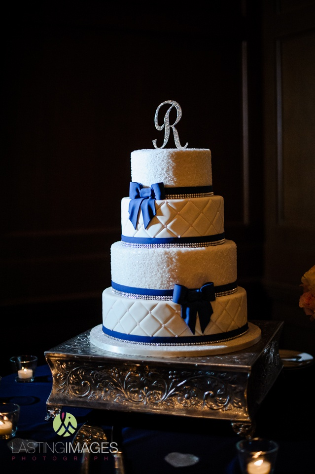Four-tier wedding cake with alternating quilted and sugar crystal layers; royal blue fondant bows and rhinestone cake topper | Lasting Images Photography | villasiena.cc