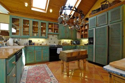 here's a kitchen with traditional cabinets painted turquoise combined with wood counter tops and terra cotta tile floor