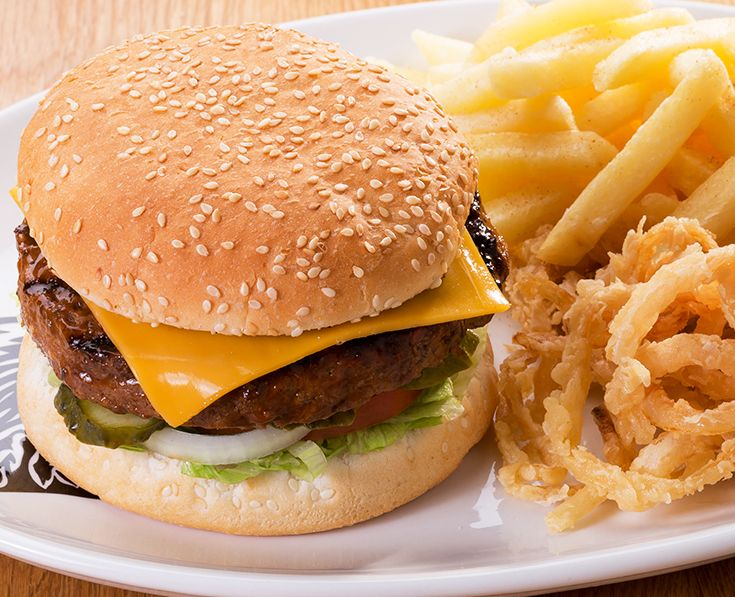 """Cheese Burger: Tuck into our single or stacked """"cheesy"""" burger - beef, chicken or soya patties served with tomato, onions, gherkins and lettuce. Topped with Melted cheese."""