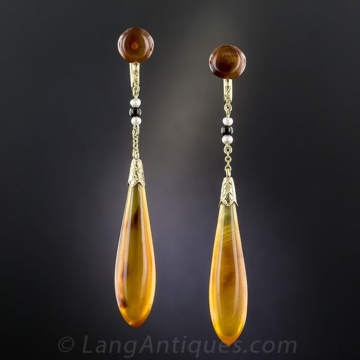 Art Deco Amber Teardrop Dangle Earrings By Day, Clark & Co. Two-and-a-half inches long, lithe and lovely, here is a rare and wonderful pair of Art Deco ear drops featuring (rather unusually) a streamlined pair of amber pendeloques. The 1 1/2 inch long drops swing and sway from amber buttons, punctuated in between by a pair of small lustrous pearls and a black onyx. These were made by Day Clark & Co., established in 1873 and in business until 1935 in Newark, NJ.