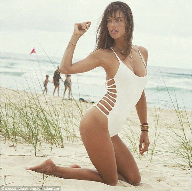 Tan lines and sunshine: On Thursday, Alessandra Ambrosio slipped on a white bathing suit with cage detailing along the sides for a steamy Instagram picture