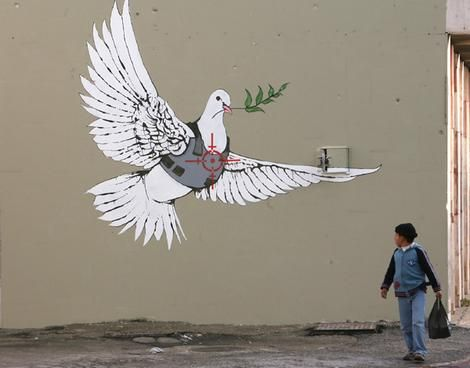 A Palestinian boy looks at one of six new images by British street artist Banksy, as part of a Christmas exhibition in the West Bank town of Bethlehem