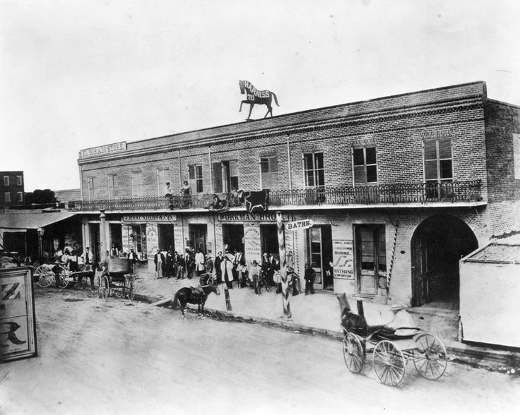 E. side of Main Street btwn Commercial and Requena Streets, 1868 (00059282) | jpg2.lapl.org/pics49/00059282.jpg  Workman Brothers Saddlery - View of Workman Brothers Saddlery shop located in a two story, brick commercial building on Main Street between Commercial and Reguena. The shop has J.B. Saunders retail store on one side and a bathing emporium on the other. A large silhouetted sculpture of a prancing horse sits atop the building.  1868