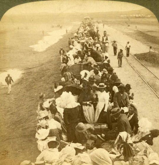 View of civilian refugees on the first train out of Kimberley after the lifting of the Siege of Kimberley during the Boer War in South Africa, February 22, 1900. Published by Underwood and Underwood.