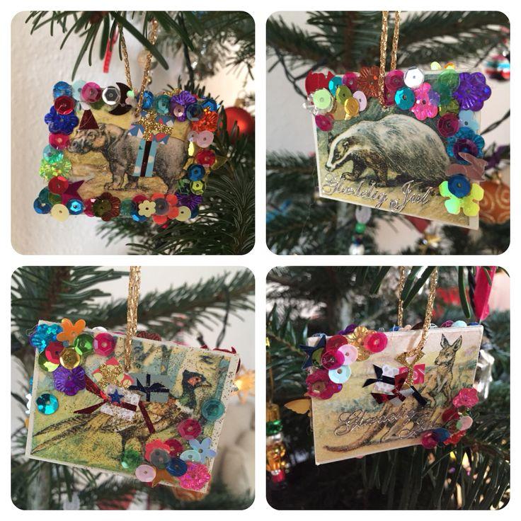 Julepynt lavet af brikker fra et billedelotteri, pyntet med palietter og små udklip med pakker.