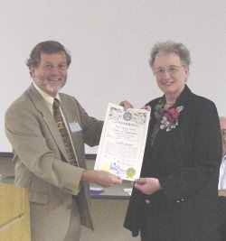 Photo of Peter Levitov presenting longtime Lincoln City Libraries Director Carol Connor with an Admiralship