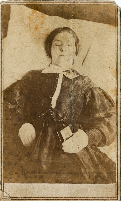 Said to be an army hospital nurse, this post mortem (death portrait) photograph shows a young woman holding a book, possibly a small bible or testament. The revenue stamp on the back dates this image to 1864. Annapolis was the site of one of the largest Union Army Hospitals during the Civil War and at least 5 female nurses died of diseases caught while tending patients there. Three of them died in late 1863 and two died in early 1865. The 1864 stamp on this image places it between those two time: Death Portraits, Post Mortem, Civil War, Union Army, Posts Mortem, Army Hospitals, Revenue Stamps, Postmortem, Hospitals Nur
