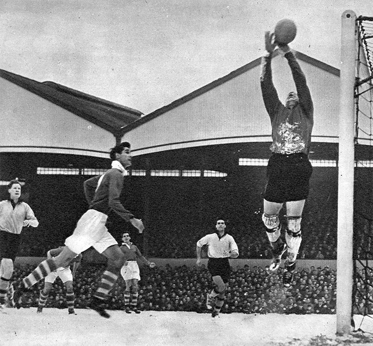 22nd January 1955. Wolverhampton Wanderers goalkeeper Bert Williams catching the ball under pressure from Charlton Athletic's John Hewis, on a snowy Molinuex pitch.
