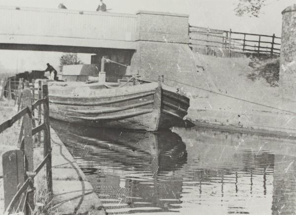 """Caption: """"Wide boat being towed at Three Bridges in Hanwell on the Grand Junction Canal"""""""