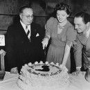 M-G-M overlord Louis B. Mayer and William Powell watch as Myrna Loy cuts her birthday cake on the set of Another Thin Man
