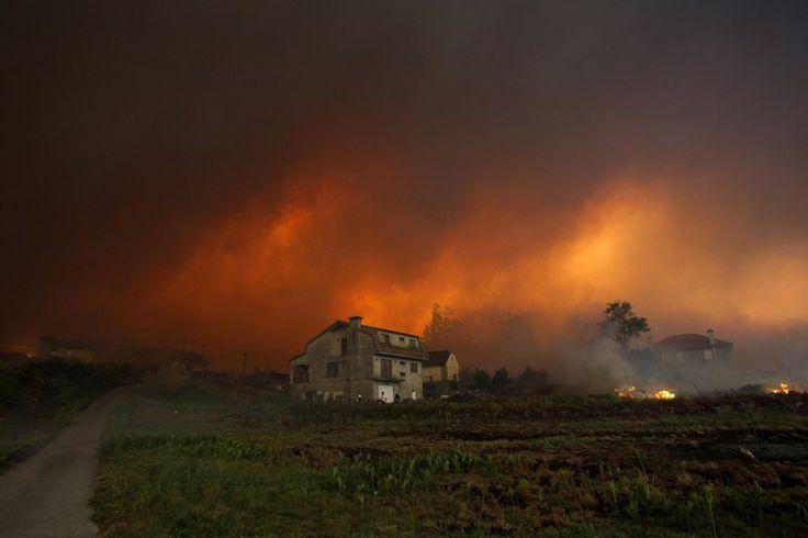 Imagen de las llamas de uno de los incendios forestales que arrasan Galicia, acercándose a las viviendas situadas en la parroquia en Chandebrito, perteneciente al municipio pontevedrés de Nigrán.