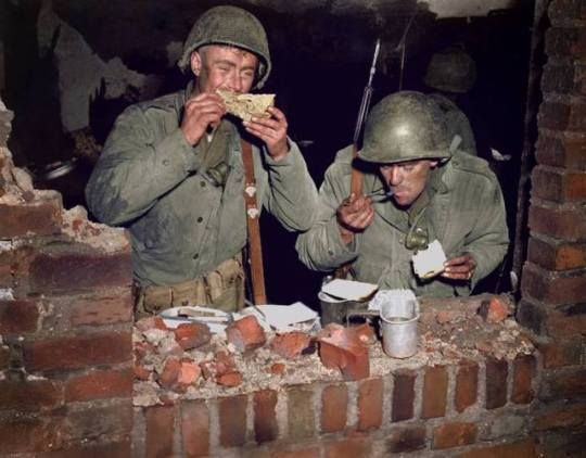 U.S. Army Infantrymen Pfc. William G. Curtis of San Diego, California and Pfc. Donald R. Stratton of Colville, Washington of the U.S. 102nd Infantry Division have time for a very brief Thanksgiving Day dinner in a shelled house. 23 November 1944.