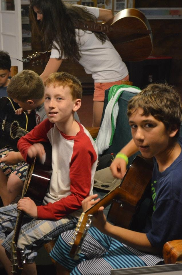 Practicing guitar skills at camp Kitchikewana