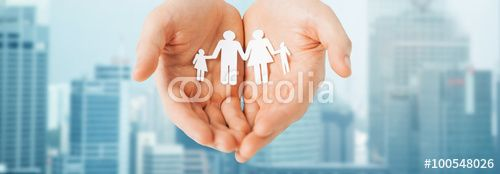 man hands holding paper cutout of family