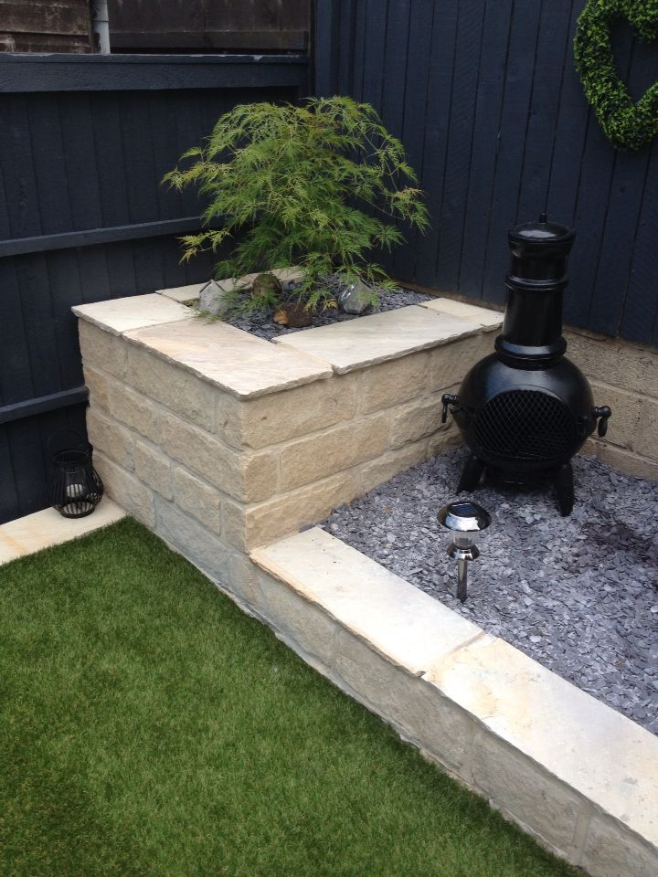 Stone built planter with acer tree with garden light and wall with blue slate chippings to flower beds