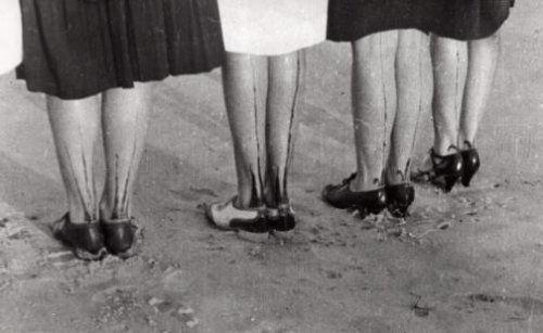 Beschilderen. Vier paar vrouwenbenen waarvan de achterkant  met verf strepen zijn beschilderd. Zonder plaats, 1931.