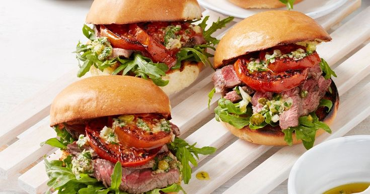 For a deliciously easy burger top fresh brioche buns with thinly sliced barbecued steak, parmesan dressing, rocket and grilled tomatoes. Recipe by Curtis Stone.