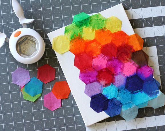 papercrafting tutorial: Fiskars Hexagon punched tissue paper on a canvas ... wet it, and it will bleed onto the canvas and into other colors ... leave it dry ... pull off the bright papers and admire the soft watercolor look left behind ... would be an awesome background for cards ....
