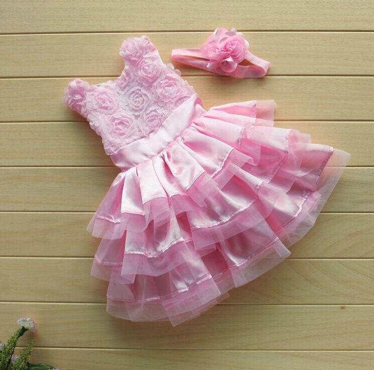 Lichtroze feestelijk babyjurkje met bloemen op het bovenpand en glanssatijn met tule-strookjes op het rokgedeelte. Het jurkje heeft een ritssluiting en striklint op het achterpand. Inclusief haarband met bloem.  Model: Leyla