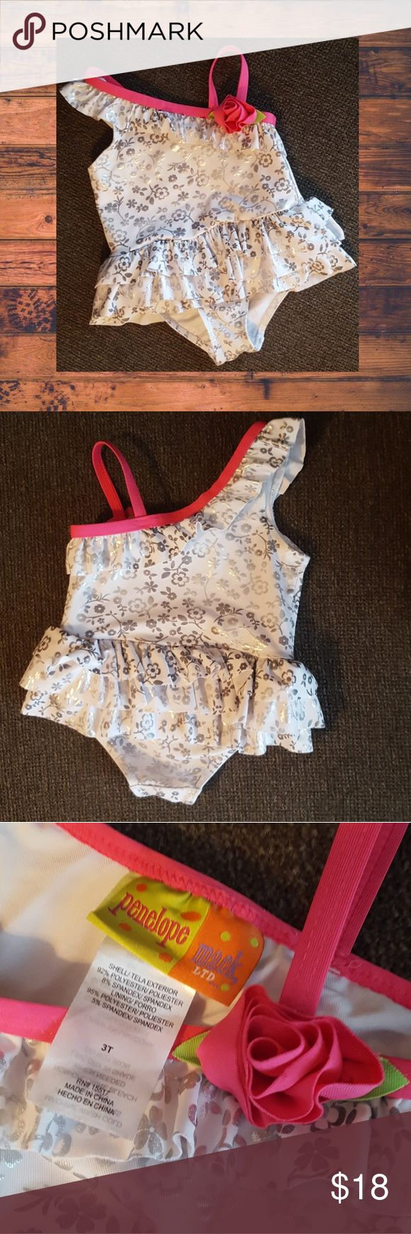 ADORABLE, NEVER WORN! Metallic Silver One Piece So cute, one piece silver metallic suit with ruffle and rose detail.  My little one never wore it due to being to small once our swim season came along. Penelope Mack Swim