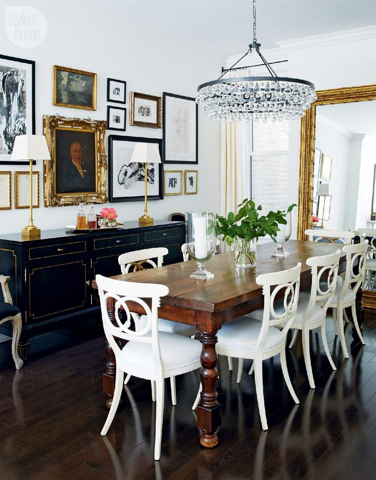 Love this dining room - warm toned wood table, white painted chairs, navy/black sideboard, slightly funky chandelier, white walls, gallery. Maybe add a rug.