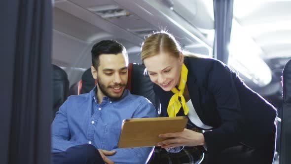 Airplane Stewardess/ Flight Attendant Shows Tablet Computer with Menu to Hispanic Male Passenger.