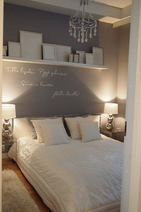Wall colour all round, shelf with gold, white and silver frames, white and grey bedding.