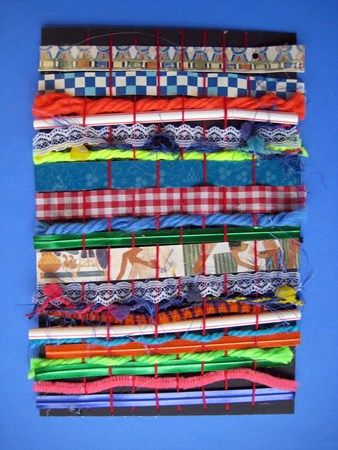 Kindergarten Weavings with ribbon, pipe cleaners, yarn, paper, straws. Looks to be on posterboard.