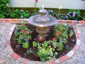 Recycled brick garden edging makes for a fancy fountain and landscaping feature!