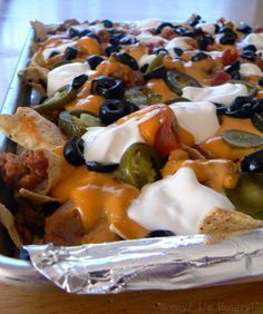 Loaded Nachos Line a cookie sheet with foil, sprayed with non stick spray. Add a layer of chips, add ground beef, beans, salsa, cheese and jalapenos. Heat in oven for about 10-15 minutes. Add olives and sour cream and Enjoy!