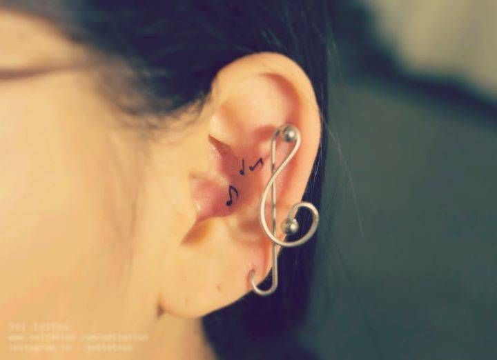 Tiny music note tattoos on the left ear.