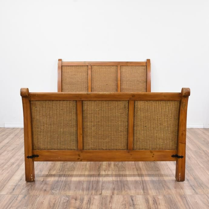 This tropical bed frame is featured in a solid wood with a glossy medium pine finish. This queen sized bed is in great condition with woven wicker panels, a curved headboard and footboard and iron metal details. Beach chic bed perfect for a beachy bungalow!·Number_of_pieces: 1   ·Condition: Very good   ·Material: Metal, wicker, wood   ·Dimensions: 64x87x49   Available now on Loveseat.