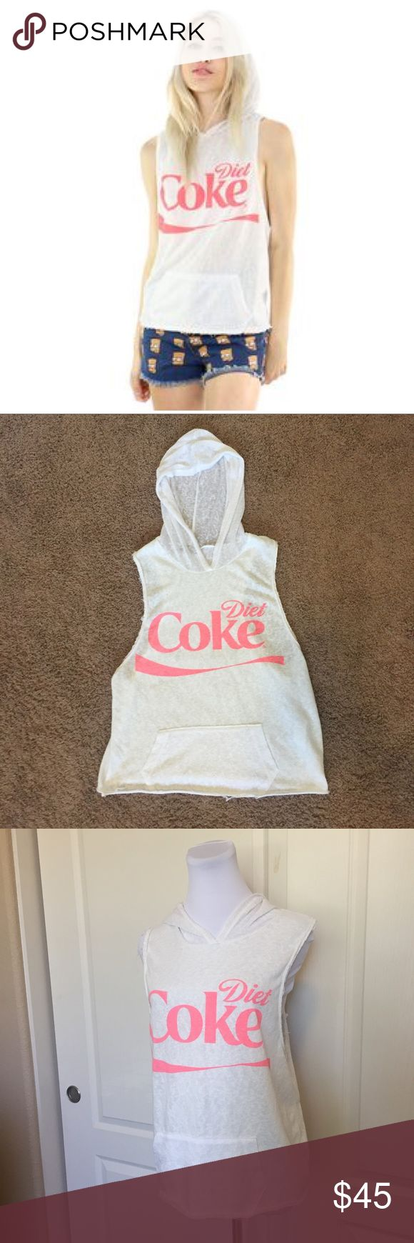 "Diet Coke Sleeveless White Raw Edge Hoodie M Diet Coke sleeveless white hoodie. Medium. Muscle tee / tank top style. ~24"" long from top of shoulder to bottom & ~19"" across the bottom of the low-cut arm holes. The fabric feels like a lightweight terry. It has a worn-in, vintage look and feel to it. Lots of stretch. 70% poly 20% cotton 10% rayon. Raw cut edging outside of the seams. Kangaroo-style hooded sweatshirt pocket. Neon orange/pink lettering. Worn once. No flaws. From Urban Outfitters…"