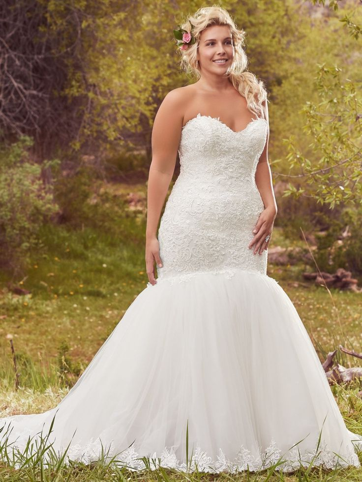 Maggie Sottero - LANSING, Exquisite lace hugs the bodice of this romantic fit and flare plus size wedding dress, before falling into a dramatic tulle skirt, edged in delicate lace. Finished with sweetheart neckline and corset closure.