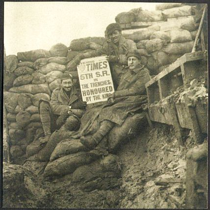 Three soldiers, perched on a pile of sandbags in a corner of a muddy, sandbag walled trench, hold up a copy of the Evening Times showing the headline which fills the front page: '5th S.R. in the trenches: Honoured by the King'.
