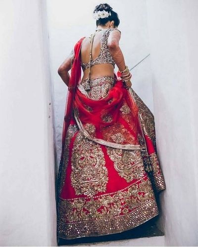 Bridal Lehengas - Red Bridal Lehenga with Gold Embroidered Motifs, Backless Blouse and Red Net Dupatta | WedMeGood #wedmegood #indianbride #indianwedding #lehenga #red #bridal #bridallehenga