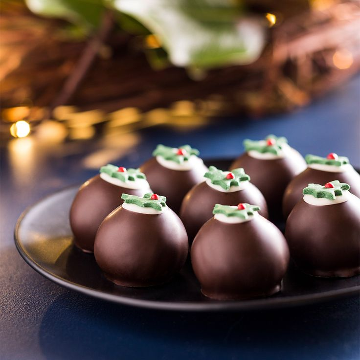 The iconic Haigh's Christmas Pudding Brandy Truffle. A Christmas favourite - a delicious brandy flavoured truffle pudding, enrobed in dark chocolate, topped with white chocolate and a holly decoration. Available individually or in gift boxes.
