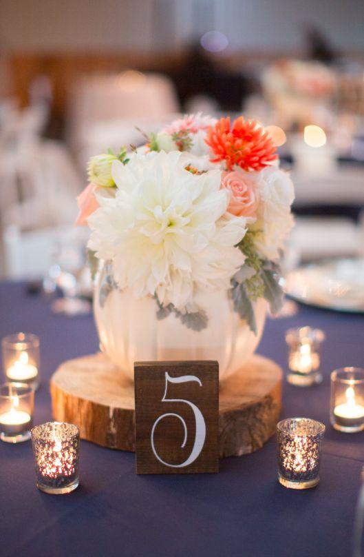 Centro de mesa con calabaza y flores blancas con toque de color, tronco y velas