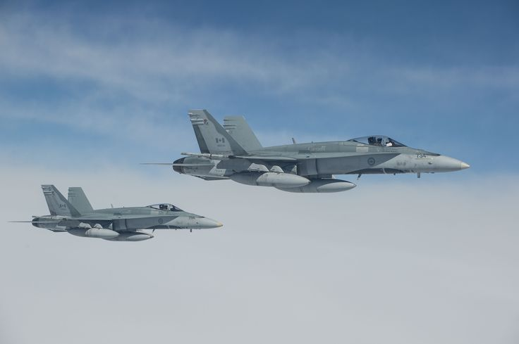 Tail Number (734 & 756): Two CF-18 Hornets from 425 Tactical Fighter Squadron in Bagotville, Québec are flying over the North Atlantic Ocean after departing Keflavik, Iceland in support of NATO reassurance measures on May 1, 2014.   Photo by Master Corporal Roy MacLellan, 8 Wing Imaging (TN2014-0142-038)