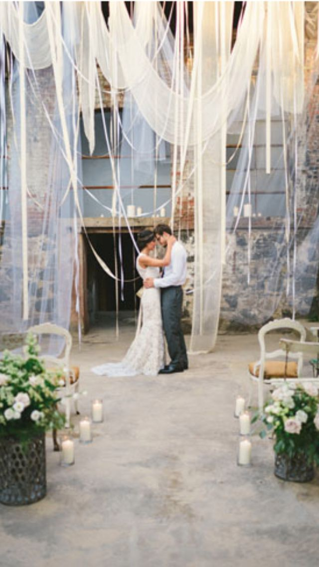 Dramatic wedding backdrop created with layers of sheer fabric and ribbon. #ceremony #decor