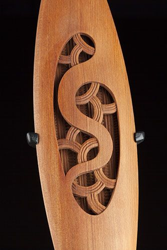 """Medium: tōtara, muka (New Zealand flax fibre), feathers (weka), MDF base. Size: 13 x 9.5 x 4.5 inches (on base). """"The piece is a contemporary take on a traditional instrument which is usually made of one piece of timber. I've used two seperate bits of totara which gives a hollowed effect""""."""