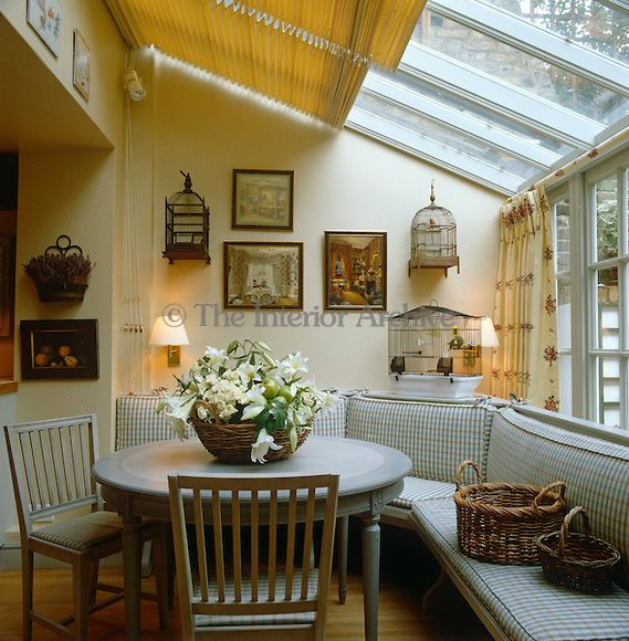 A dining area with an upholstered banquette is housed in a for Conservatory dining room design ideas