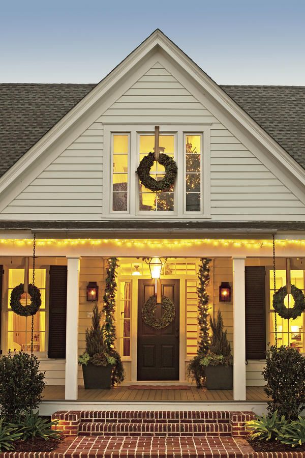 Merry and Bright - These Porches Got a Merry Makeover for the Holidays - Southernliving. The decor starts with a simple arrangement of wreaths and garland. The golden, glowing lights bring major Christmas cheer to the home.