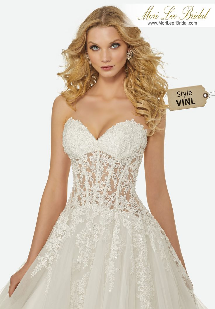 Style VINL SERENA WEDDING DRESSCrystal Beaded, Cascading Venice Lace Appliqués on a Strapless, Sweetheart, Sheer Bodice with a Full A-Line Tulle Over Sparkle Tulle Skirt.Colors:IVORY, IVORY/LIGHT GOLD
