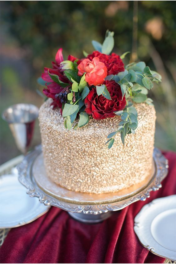 small gold wedding cake with red blooms and greenery