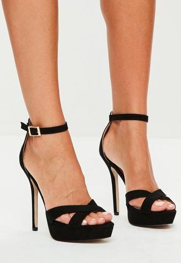 Des sandales noires à talons hauts avec une plateforme, deux lanières croisées, et une fermeture à bride autour de la cheville