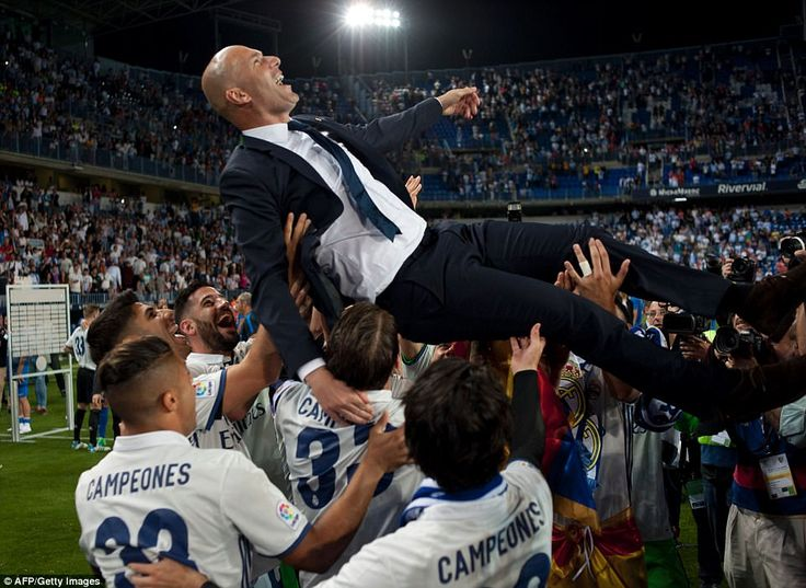 Real Madrid lift head coach Zinedine Zidane after they seal their first La Liga title in f...