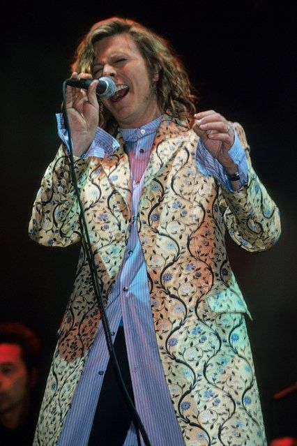 2000 Wearing a floral embroidered dress coat and striped shirt on stage at Glastonbury.