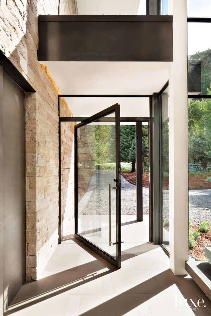 Architects Rich Pavcek and Charles Cunniffe designed a contemporary structure that makes the most of its proximity to the Roaring Fork River in Aspen. A generously proportioned steel-and-glass pivot door by Dynamic Architectural Windows & Doors opens to the entry without obstructing views or light.