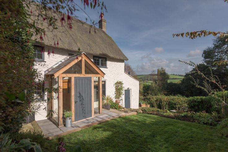 Peeking through a curtain of majestic green pines within the colourful patchwork of Dorset's countryside you'll find Theodora's Cottage,a thatched white cob cottage set near the iconic village of Burton Bradstock.